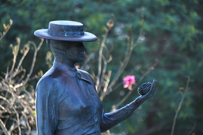 """Statue of horticulturist Kate Sessions, """"Mother of Balboa Park."""" Single rose in the park on the background."""