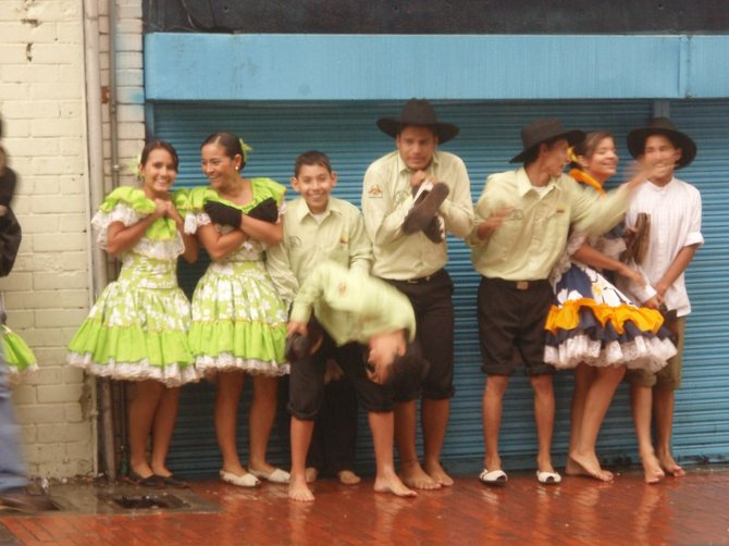A dance troupe meant to dance in the streets as part of a festival takes refuge from the sudden rain in Bogota, Colombia