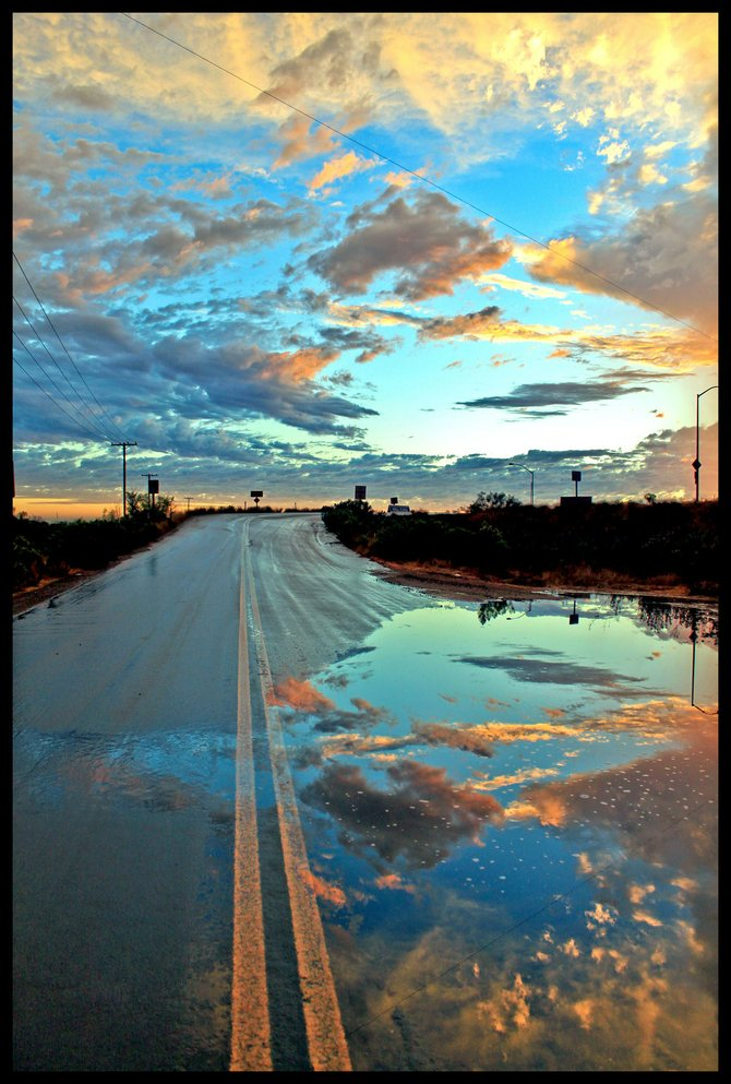 As I drove home on the day we had the recent rain storm the clouds began to part and revealed this magnificent fall sunset. I pulled off the 163 onto Kearney Villa Rd and this was the first street I found. The puddle adds a third dimention to the scene...I love it and hope you do too! Taken on September 30, 2010