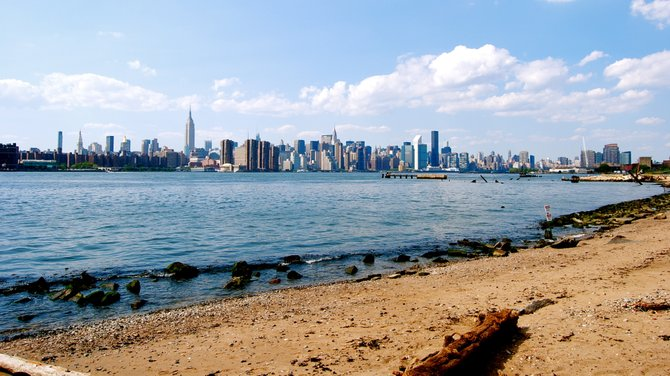 View of the Manhattan skyline from the East River park located in the Williamsburg neighborhood of Brooklyn.