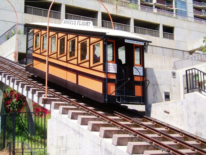 The Angels Flight Railway in Los Angeles is the shortest railway line in the United States. It climbs 298 feet up a steep slope between Hill Street and the Panama Plaza in downtown Los Angeles. It was originally built in 1901 by Colonel J.W. Eddy and is one of the few funicular railways in the United States. A funicular design involves two counterbalanced train cars attached by a cable on a pulley system, traveling on parallel tracks. The weight of one car moving downward pulls the second car upward along the incline.