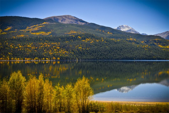This photo was taken recently on a clear day in Twin Lakes, Colorado. The reflection of the Rocky Mountains and its Aspen trees displaying their fall colors on the smooth water surface of Twin Lakes was absolutely magical.