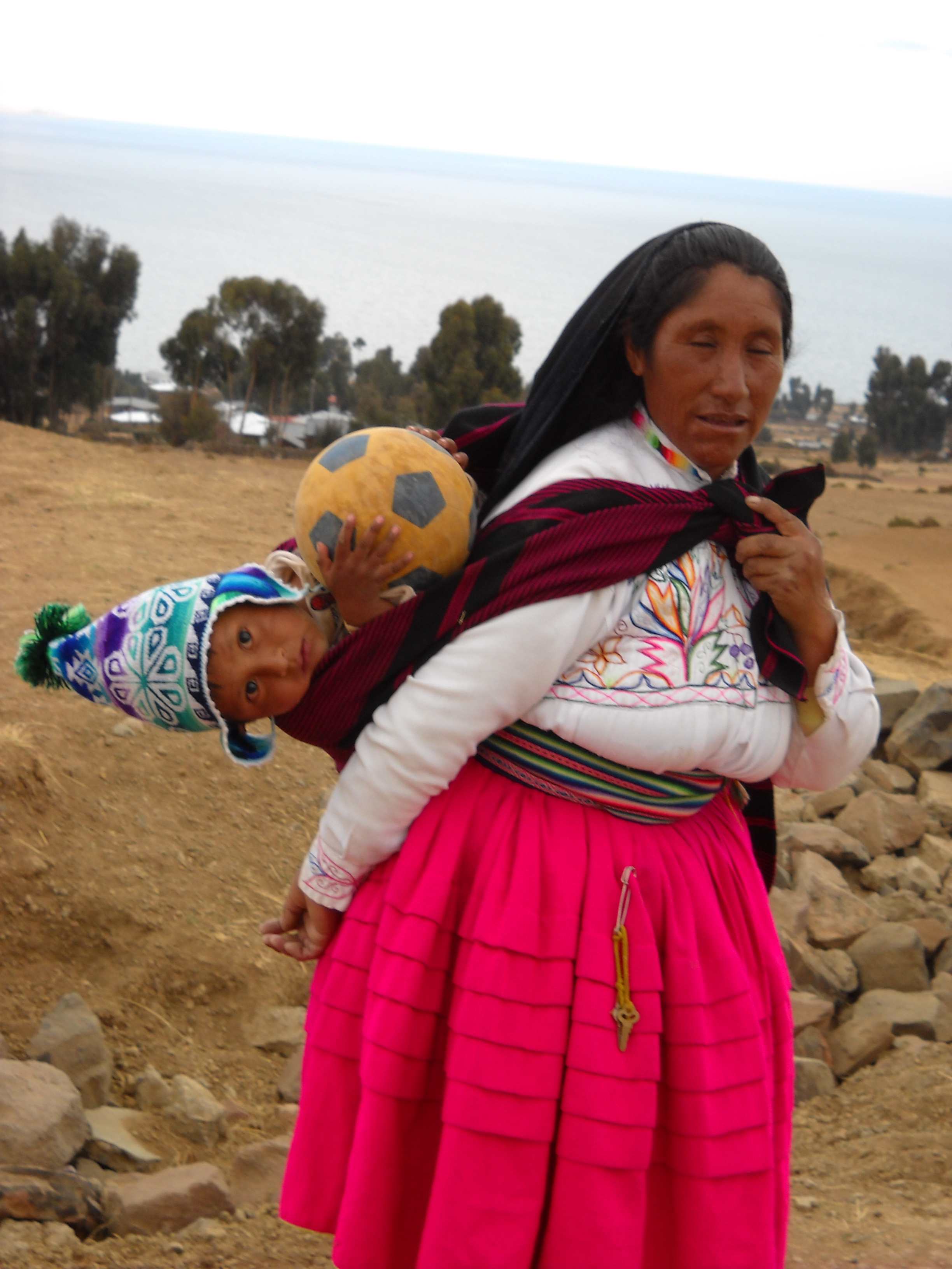 Lake Titicaca, Peru. Local attire for woman who hikes up a mountain and back to sell goods that are in the sack on her back. Soccer is a local pastime and from a young age children are enthusiastic about playing.