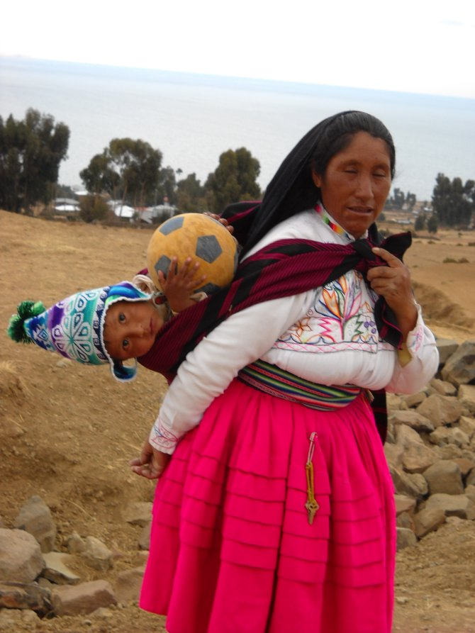 Lake Titicaca, Peru. Local attire for woman who hikes up a mountain and back to sell goods that are in the sack on her back. Soccer is a local pastime and from a young age children are enthusiastic about