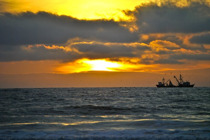 a fishing boat with a sunset.