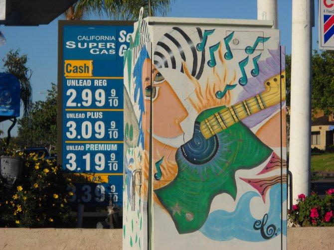 Garnet Avenue utility box art framed by gas station price signage.