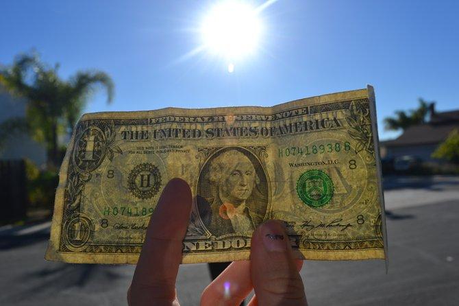 A crisp dollar bill, lens flare.