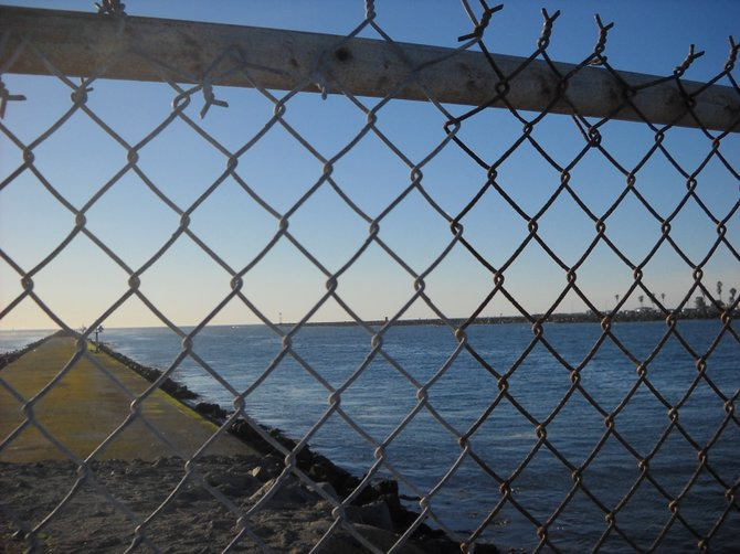 Looking through the rusty fence of the Mission Beach jetty on a winter's day.