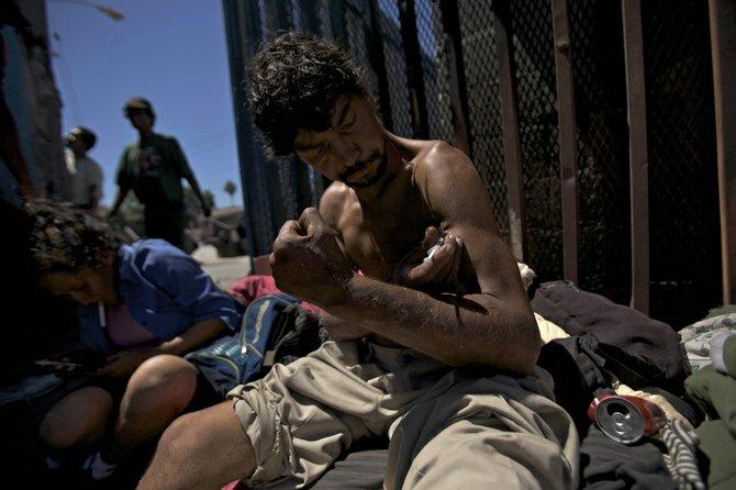 A Tijuana heroin addict shoots up near the border fence.