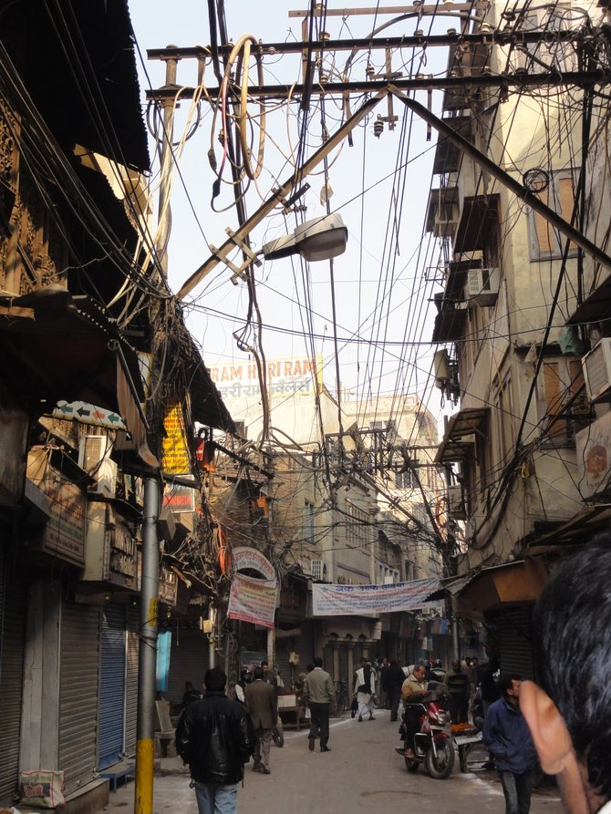 The streets of Chandi Chowk are narrow, crowded and full of overhead wires ... along with great deals at every store.