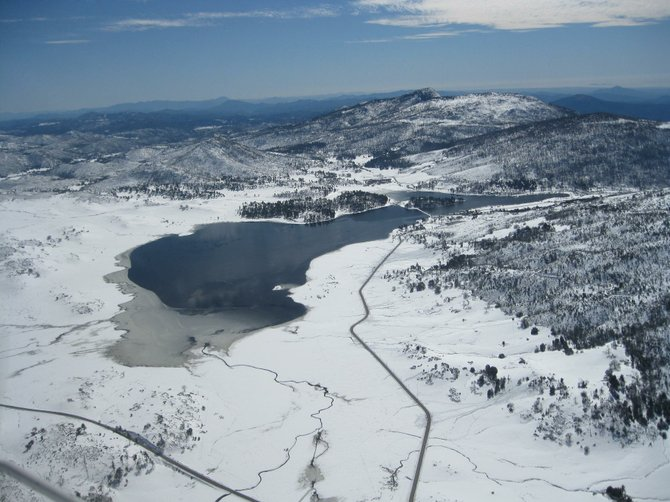 Lake Cuyamaca surrounded by snow an ice on Monday, Feb 28. Taken from a private aircraft 7000' above sea level, about 1500' above the ground.  I believe that's Stonewall Peak in the background.