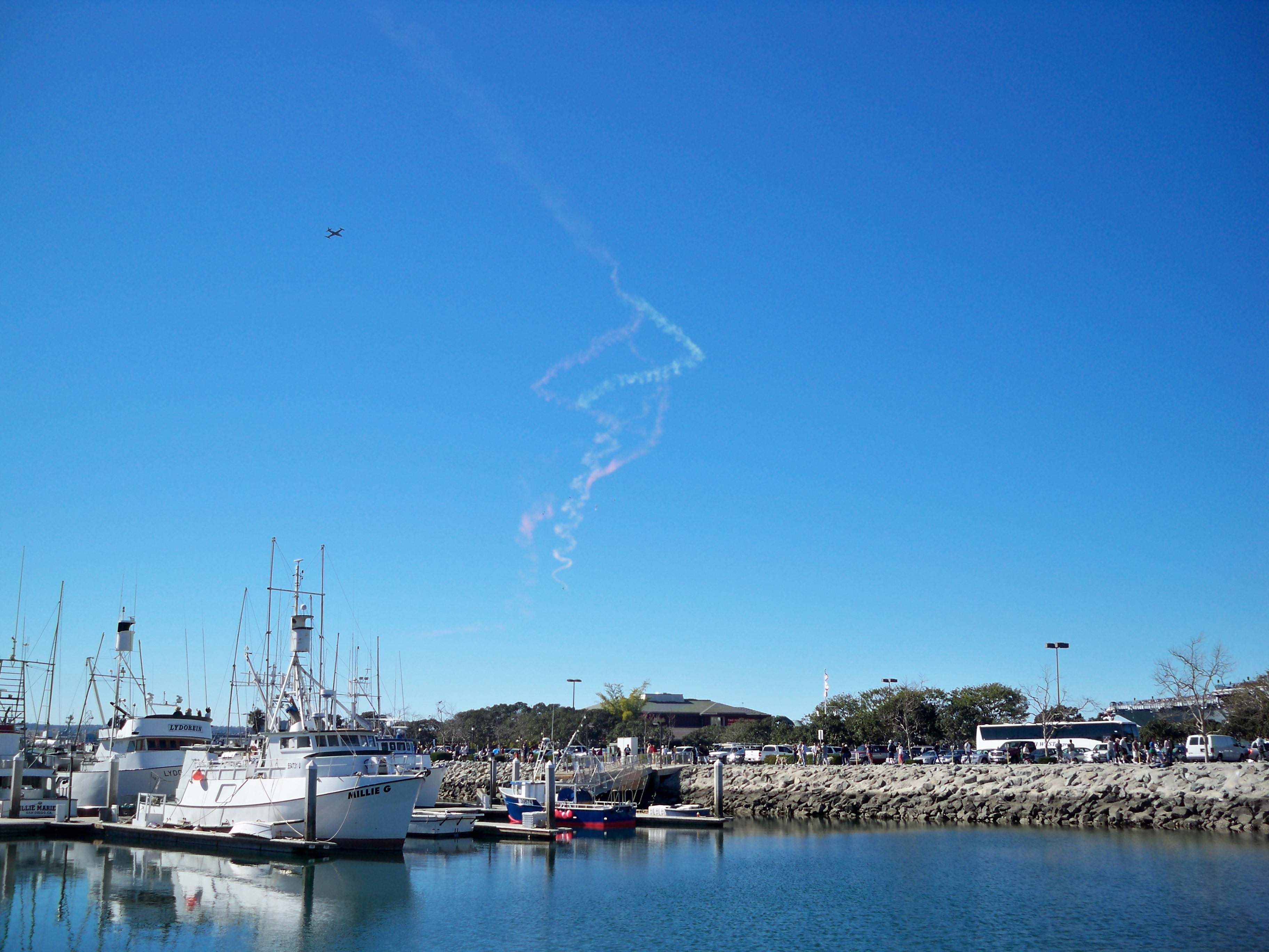 Skydivers letting out smoke trails as they glide past the Fish Market downtown.
