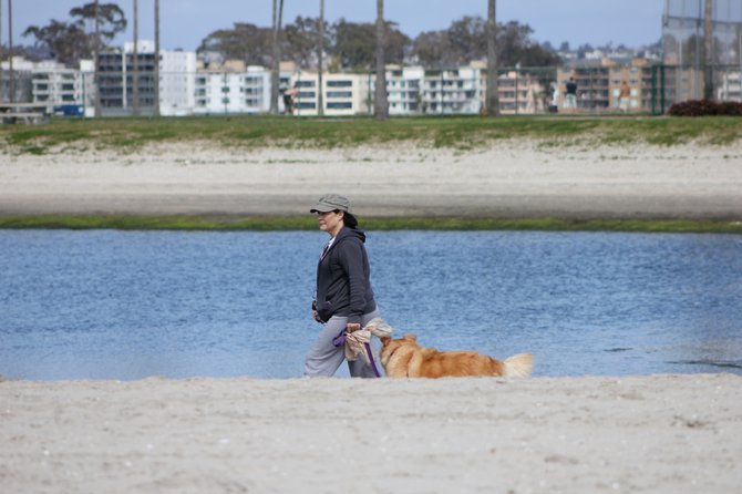 Local taking her dog for a walk near Santa Clara Place in Mission Beach