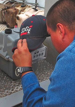 An SDG&E worker installs a gas meter with a smart-meter module.