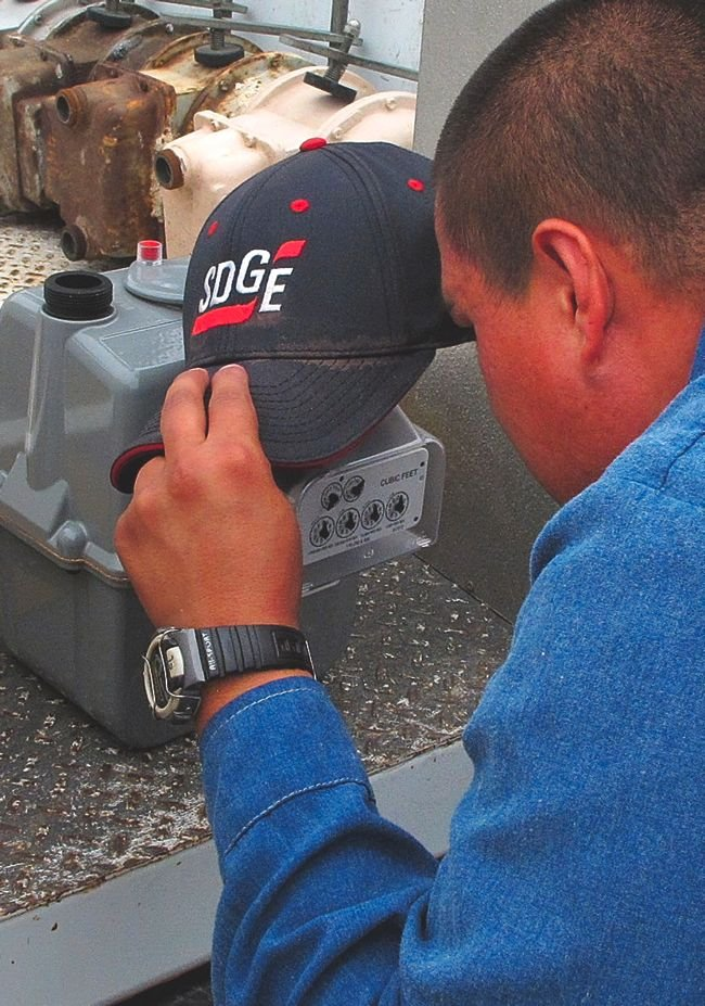 An SDG&E worker installs a gas meter with a smart-meter module.