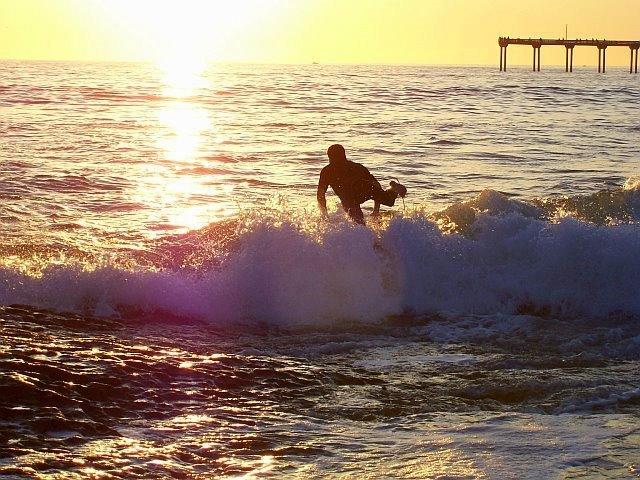Surfer launching off Sunset Cliffs.