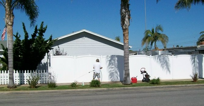 An Imperial Beach resident pressure-washes his fence that had been tagged with graffiti.