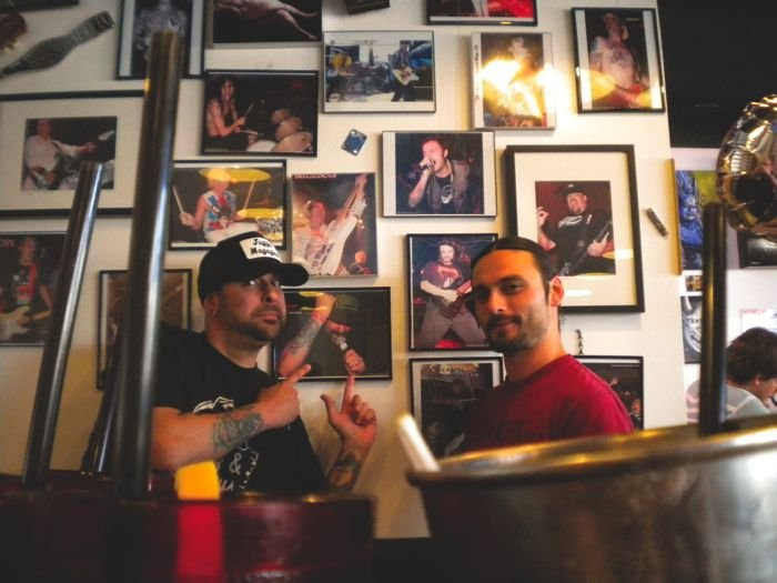 Employees like it here because they can fill in for each other when their bands get to tour. Nick Bone, of the Screamin' Yee Haws (in cap), and Jake Phillips (Downspell) in front of their publicity shots