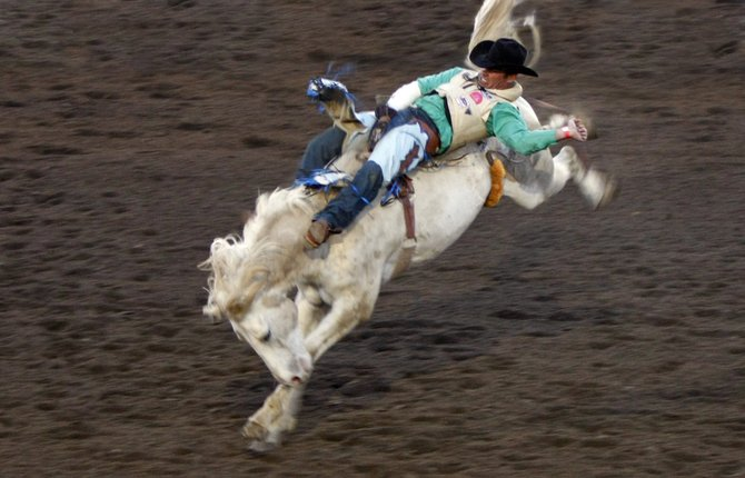 A cowboy tries to hang on at the Ramona Rodeo.