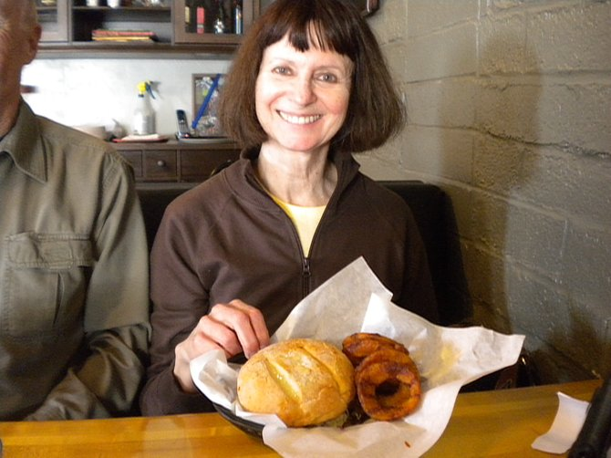 "Marjorie, showing off her sandwich (it's called ""the best pulled pork under the bun"")"