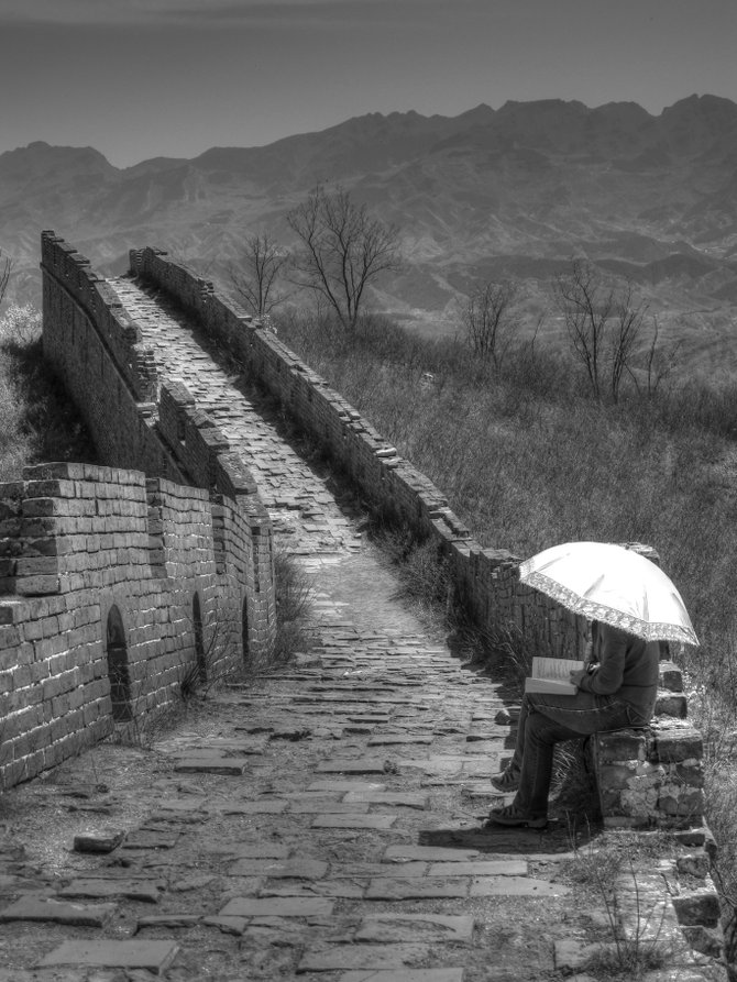 A girl is lost in a book while sitting on the Great Wall
