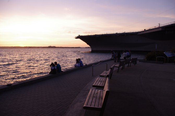 Young couples enjoy the sunset at the harbor side next to the historical aircraft carrier USS Midway.