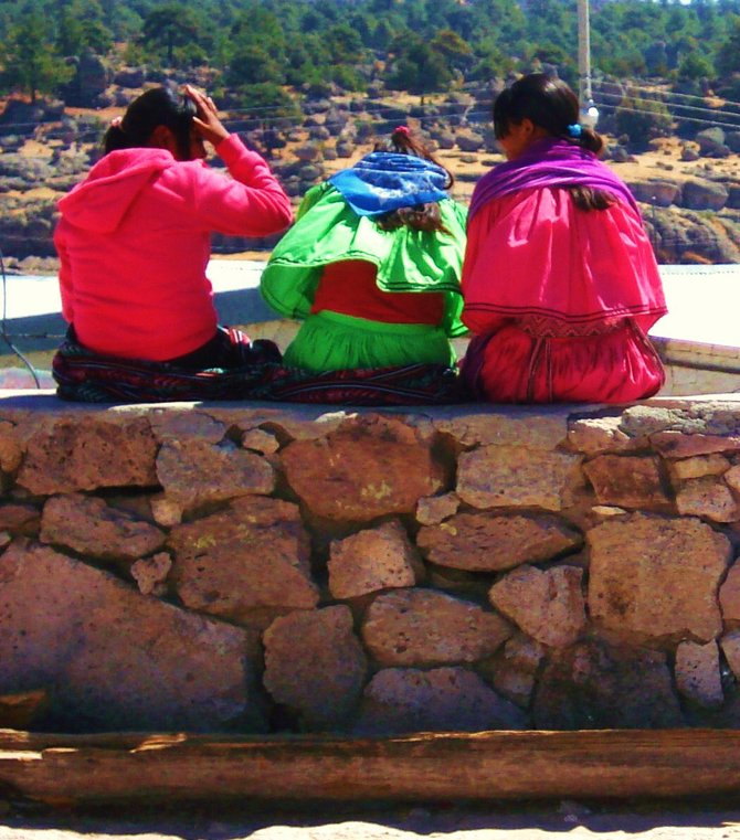 Tarahumara girls sitting on a wall outside the mission school.
