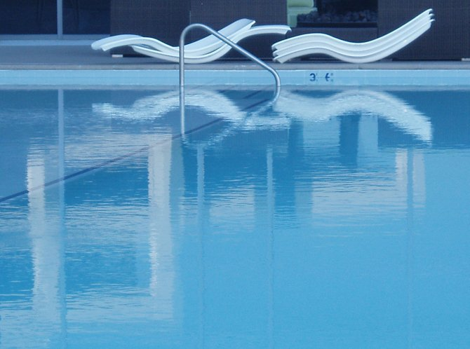 A reflection of the deck chairs in the pool at the Valley View Casino on a hot July day.