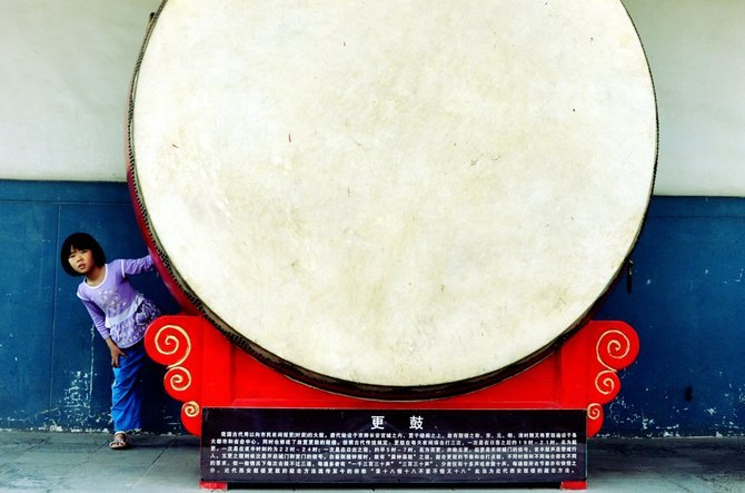 I was traveling in China last month.  Walking around the drum tower in the center of the city of Xi'an... I happened to capture this girl peaking out from behind one of the big drums.