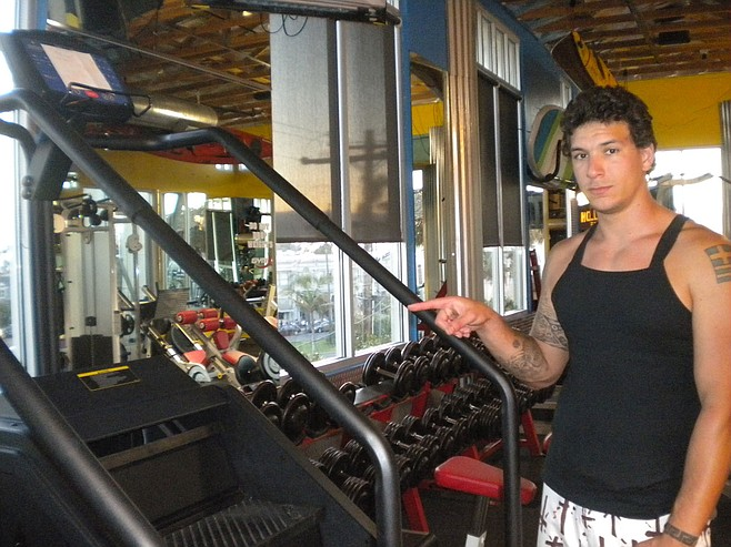 Desi Ochoa, trainer at Hollywood Fitness, points out equipment used by Zahau.