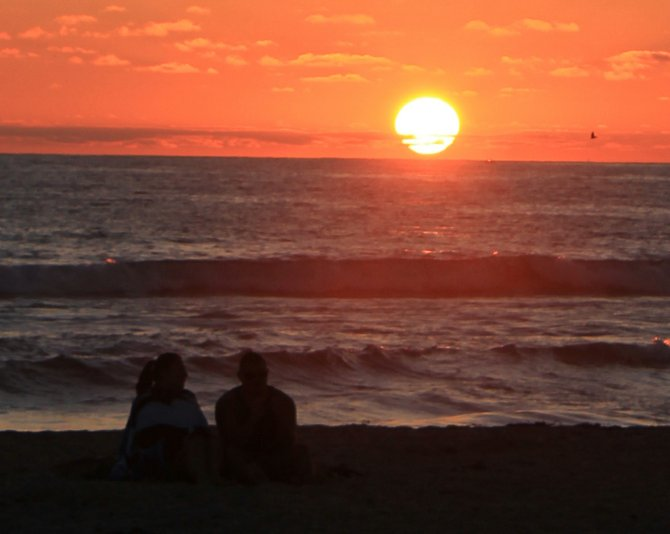 I was waiting with my sister Gloria, to be called for our dinner reservation at World Famous, when I spotted this couple sitting on the sand watching the sunset. I thought it made a great picture!