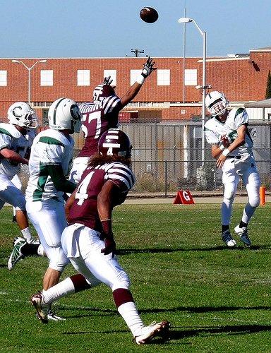 Coronado quarterback Austin Denson fires a pass over the outstretched arms of Kearny defensive lineman Ben Moa
