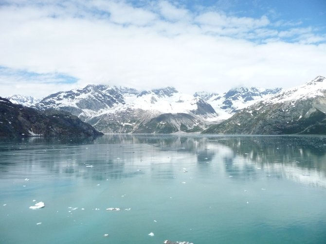 At Glacier Bay of southeast Alaska, June 2011.  The picturesque view of the mirror-like sea reflecting the snow mountains and cloudy sky.