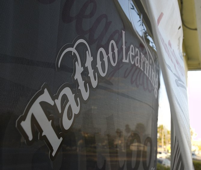 Storefront of the Tattoo Learning Center, its sign covered by a banner for Steady Flow Tattoo, at 1946 Grand Avenue.