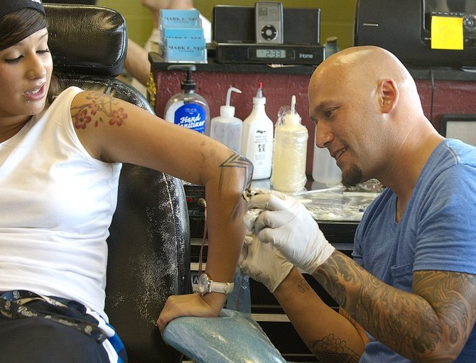 Mark Nes, the 34-year-old owner of Body Mark's in North Park, tattoos Jessica Martinez's elbow. 