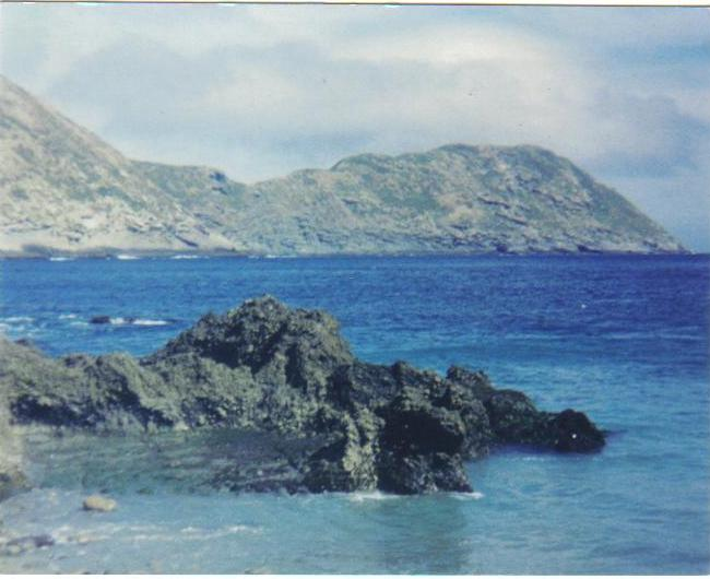 """View southeast from the cove in the lee of Middle Island, Islas Los Coronados, Baja California, Mexico... as described in my blog entry """"ILLUSION DWELLER"""" (found under """"TALES OF ADVENTURE"""" on my profile page). Photo is a bit washed out, but that's the 672' summit of South Island across the channel. Been there too, as described in """"LASERIUM"""" (also under """"TALES OF ADVENTURE"""")."""