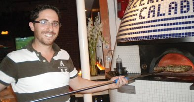"""""""No gas!"""" Giancarlo removes a pie from Caffé Calabria's """"pure wood-burning oven."""""""