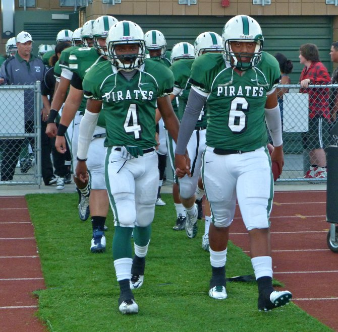 Oceanside running back Ryshaud Keegan (4) and quarterback Tofi Pao Pao (6) lead the Pirates onto the field