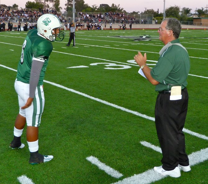Oceanside quarterback Tofi Pao Pao gets the play call from Pirates head coach John Carroll
