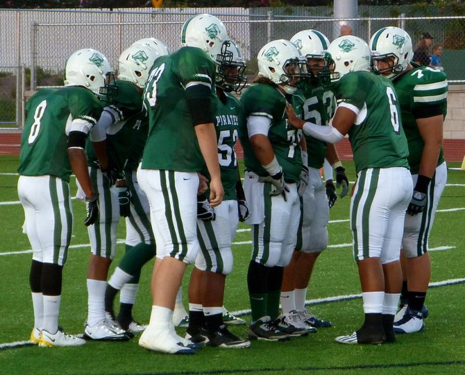 Oceanside quarterback Tofi Pao Pao calls out the play in the Pirates offensive huddle