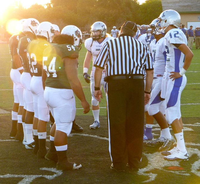 Helix and Eastlake team captains meet at midfield for the coin toss