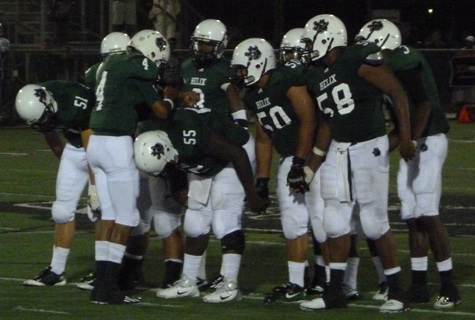 Helix quarterback Brandon Lewis calls out a play in the offensive huddle