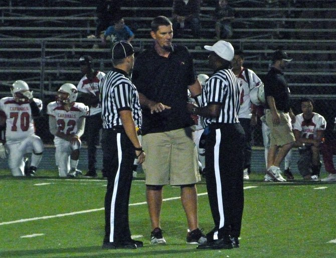 Hoover head coach Cree Morris talks things over with the officials
