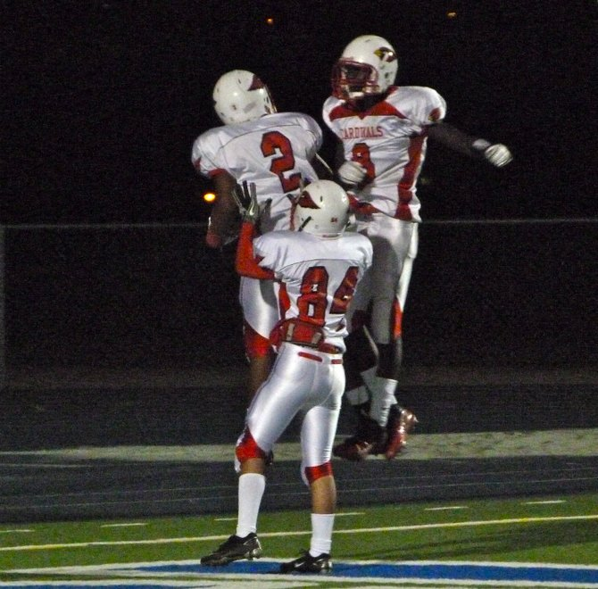 Hoover running back Damonte Holiday celebrates a fourth quarter touchdown run with a pair of Cardinals teammates