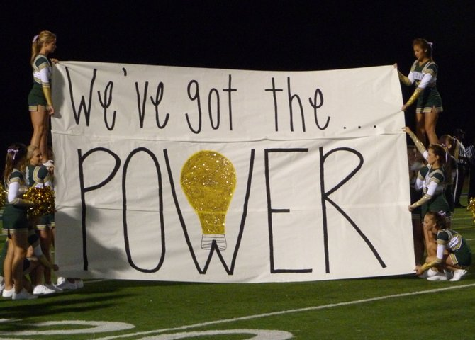 La Costa Canyon's cheerleaders hoist the halftime banner that makes light of the historical power outage the day before