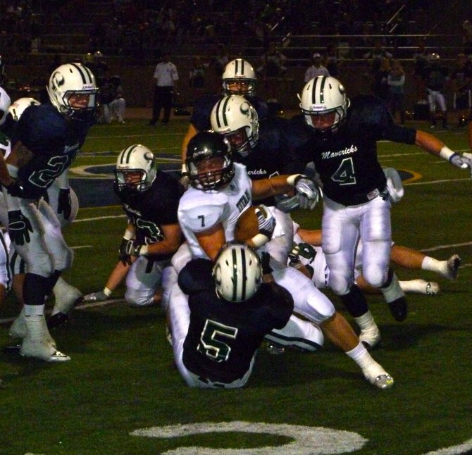 Poway receiver Conor Flanagan fights through the tackle of La Costa Canyon linebacker Trevor Dunn with Mavericks defenders closing in