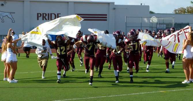 Point Loma players rip through the banner after halftime