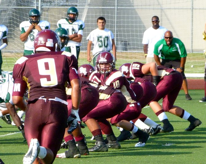 Point Loma quarterback Sam Augustine looks down the line with Pointers running back Morris Mathews (9) going in motion