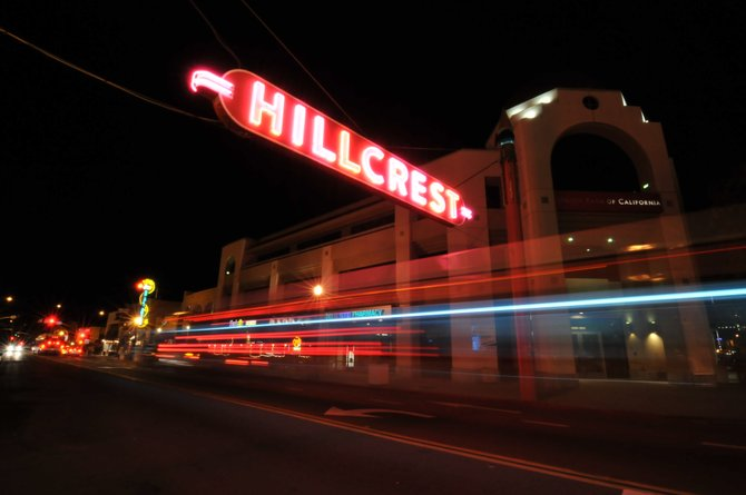 The Hillcrest sign at night on a timed exposure with the trailing lights of a city bus.