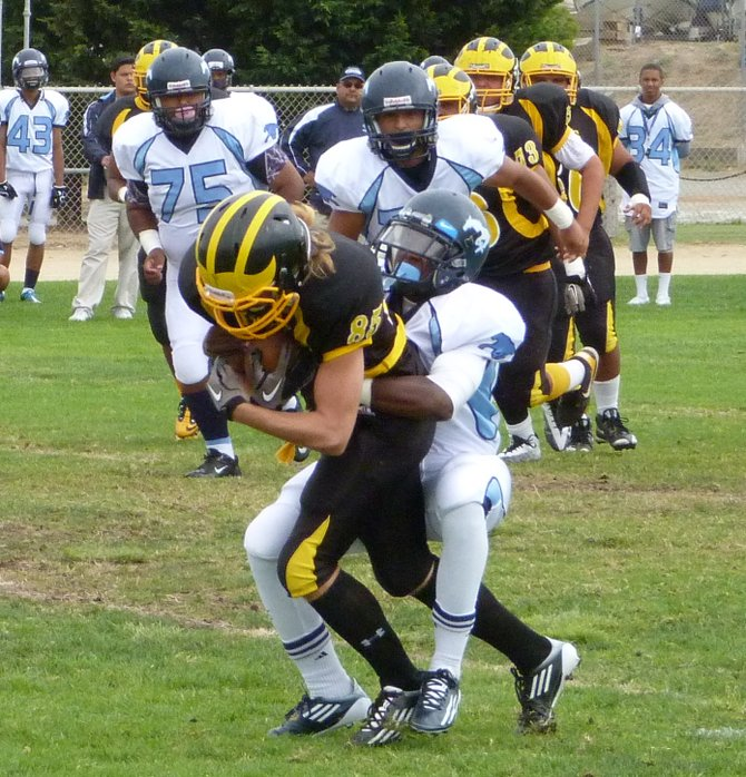 Mission Bay receiver Canaan Cruz fights trough the tackle of Otay Ranch defensive back Desean Dawson